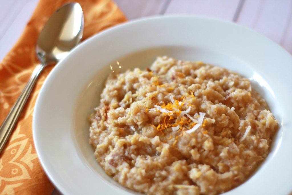 Breakfast kitcheree topped with orange zest and coconut flakes in a white bowl beside orange napkin and silver spoon