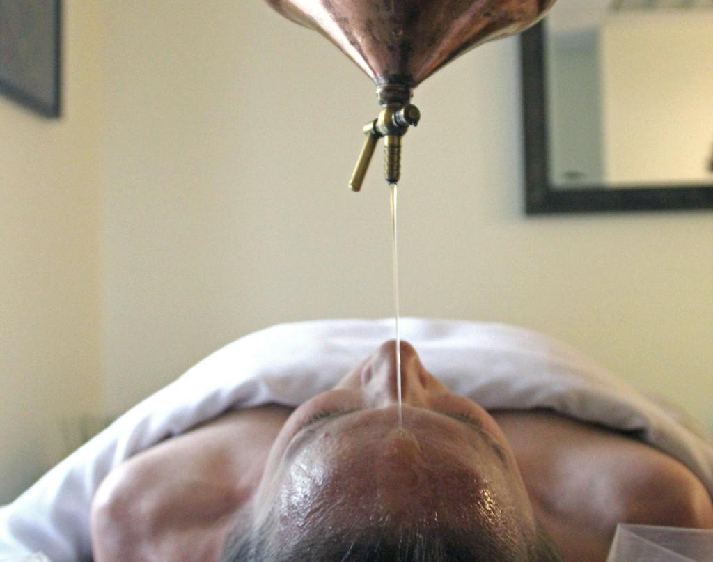 Ayurvedic Treatment - Shirodhara: Client on massage table with sesame oil streaming on her forehead from a copper vessel