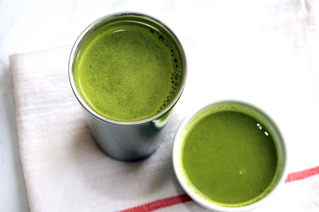 Green drinkable soup in a stainless steel thermos and white ramekin on a white kitchen towel