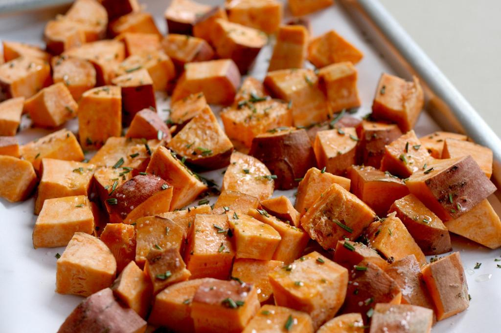 Cubed sweet potatoes sprinkled with fresh rosemary
