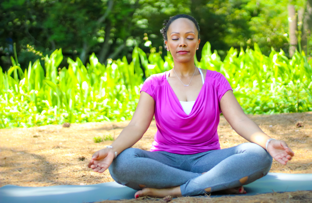 Tesia Love seated crossed leg meditating with eyes closed.