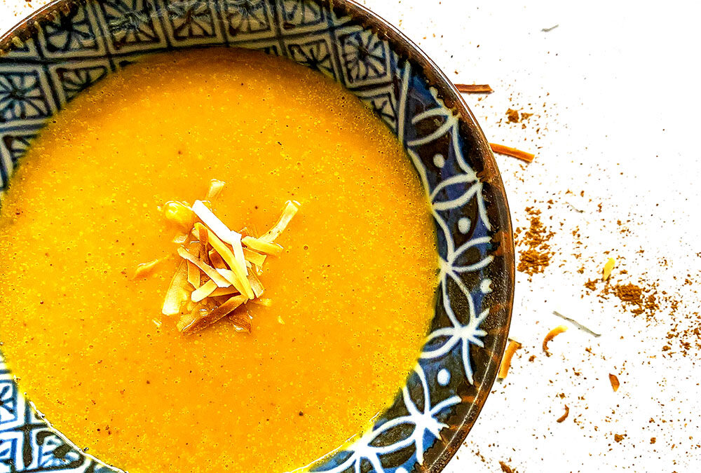 Bowl of coconut butternut squash soup garnished with toasted coconut flakes